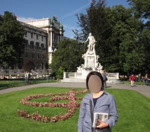 モーツァルト像とトーン記号を型どった花の植え込みの正面写真